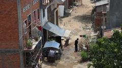Boy parks bike on slum street Cambodia high angle Stock Footage