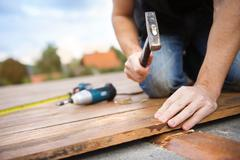 Handyman installing wooden flooring Stock Photos