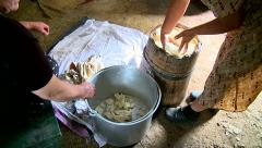 Stock Video Footage of Women take out the cheese from wood bucket
