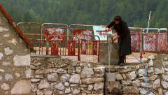 Woman pulls water from the water well and poured into a bucket Stock Footage