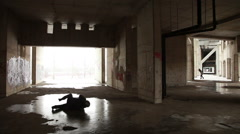 Man in the hat and coat rolling on the ice in an abandoned urban building Stock Footage