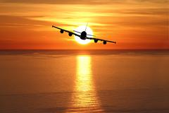 Beautiful sunset with airplane over the sea Stock Illustration