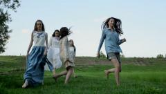Glad girlfriends jumping in a field - stock footage