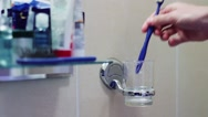 Stock Video Footage of Man puts toothbrushes in a glass