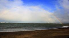 Full rainbow over Icelandic ocean beach, Grotta lighthouse Reykjavik Stock Footage