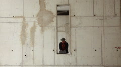 Man takes off his coat hat and red scarf in abandoned unfinished urban building Stock Footage