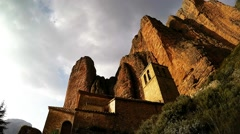 time lapse of a small monastery in the village against the backdrop of cliffs - stock footage