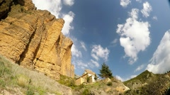 Time lapse of a big limestone cliff with small monastery in the village Stock Footage