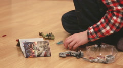 Boy playing with lego sitting on the wooden floor. Stock Footage
