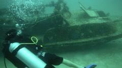 Scuba divers explore small shipwreck on ocean floor Stock Footage
