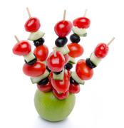 Cherry tomatoes, cucumber and olives on skewers pricked into an apple Stock Photos