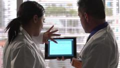 Doctors looking at medical chart on tablet Stock Footage