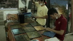 A man and woman work with with wooden artwork in a Cambodian workshop Stock Footage