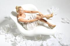 Beautiful young woman sitting on a white chair surrounded by stylish white flowe Stock Photos