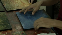 Stock Video Footage of Closeup of a woman's hands creating a piece of wood-panel artwork in Cambodia