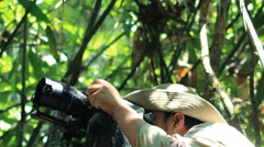 Wildlife Photographer taking picture of bird in the rainforest jungle Stock Footage