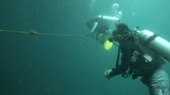 Scuba divers holding rope during compulsory safety stop on ascent Stock Footage