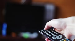 Switching channels on your TV remote control Stock Footage