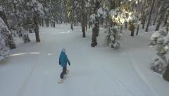 AERIAL: Snowboarding on the snowy forest path Stock Footage