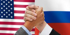 Hands armwrestling over american and russian flags Stock Photos
