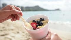 Acai bowl - girl eating healthy food on beach Stock Footage