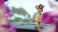 Hawaii travel car - Hula doll dancing on dashboard and lei during road trip Stock Footage