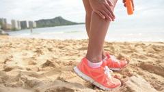 Sun screen lotion - runner woman on beach  applying sunscreen suntan lotion Stock Footage