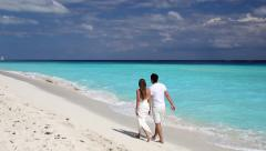 Young beautiful newlyweds in love holding hands and walking on tropical  beach - stock footage