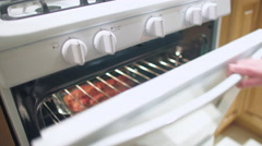 Opening oven to look at broiled pork 4K - stock footage