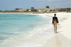 Woman in thong walking down the beach. Stock Photos