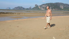 Old man walks along  beach and stretches   muscles Stock Footage