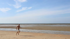 Old man runs along beach at low tide Stock Footage