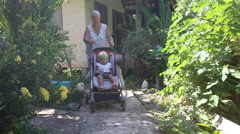 Grandmother carries blonde toddler in pram Stock Footage