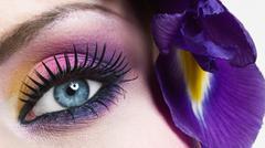Woman eye with colorful make-up and long false eyelashes - gerber flower Stock Photos