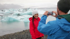 Iceland - couple taking photo with smartphone by Jokulsarlon selfie Stock Footage