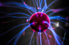 Plasma ball  with magenta-blue flames isolated on a black background. Stock Photos