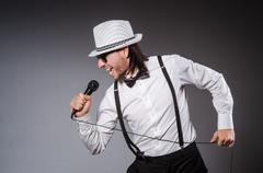 Funny singer with microphone at the concert Stock Photos