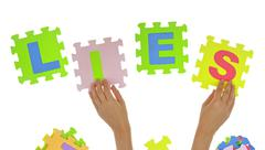 "Hands forming word ""Lies"" with jigsaw puzzle pieces - stock photo"