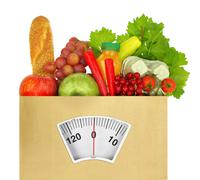 Paper bag full of groceries with weighing scale Stock Photos