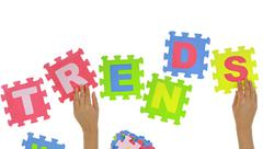 """Hands forming word """"Trends"""" with jigsaw puzzle pieces isolated - stock photo"""