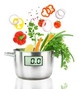 Fresh vegetables falling into a casserole pot with digital weight scale - stock photo