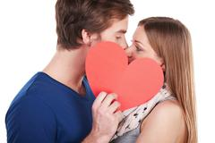 Woman and man kissing behind red heart Stock Photos