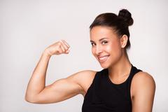 Close up of mixed race woman demonstrating biceps - stock photo