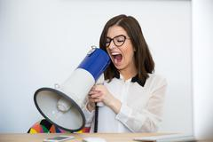 Businesswoman sitting at the table and speaking through megaphone Stock Photos