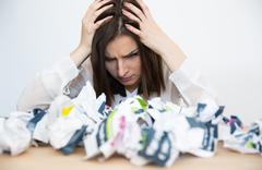 Portrait Of frustrated businesswoman sitting at the table with trash papers - stock photo
