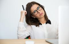 Thoughtful businesswoman sitting at the table with bank card - stock photo