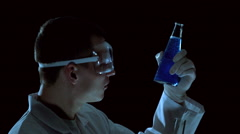 Chemist examines a test tube with blue liquid side view Stock Footage