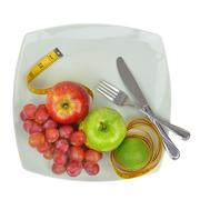 Fresh fruit and measuring tape on a plate Stock Photos