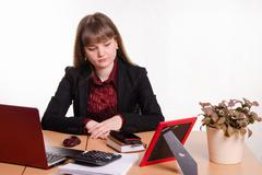 Detached woman sitting at office table Stock Photos