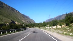 Rapid movement of the empty curved asphalt road, blue sky and sun - stock footage